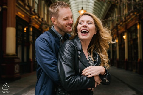 A engagement photoshoot at Leadenhall Market in London, England with a relaxed couple laughing and embracing