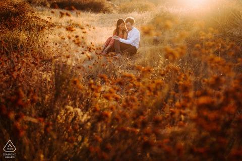 Los Angeles, Californie photographie de mariage avant un couple assis dans un champ ouvert dans la lumière du soleil de l'après-midi