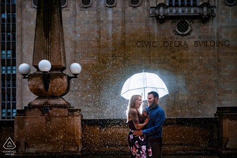 Chicago Civic Opera couple engagement portraits with a lit umbrella in the rain
