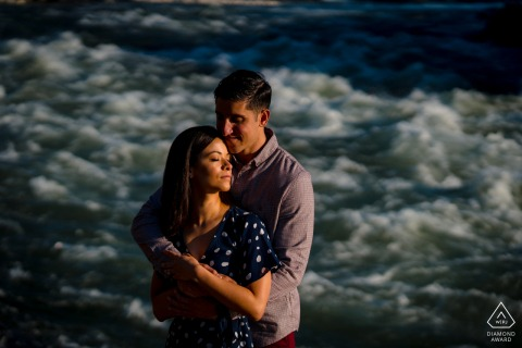 Great Falls, Virginia engagement portrait of a couple embracing in early morning light, with the raging river behind them