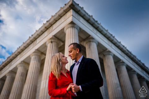 The couple embrace at the corner of the Lincoln Memorial for their engagement portrait session in Washington DC