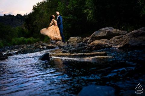 订婚的夫妇在科罗拉多州伊德代尔的巢穴熊公园的订婚照中凝视着河水