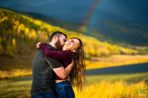 Couple embrace during an unexpected afternoon storm at their engagement session at Piney River Ranch in Vail, CO
