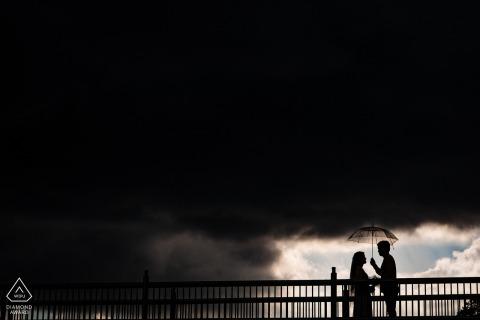Vietnam Dalat pre wedding image taken under a dark storm sky with the couple holding an umbrella