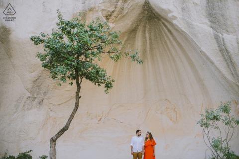 一對訂婚的情侶在土耳其的卡帕多西亞洞穴前擺姿勢