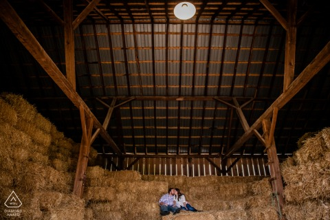 A fall engagement portrait session at a Maryland farm of the couple sitting on hay bales stacked in a barn