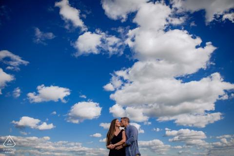 Fotografía de compromiso de Maryland en las nubes con un abrazo de pareja centrado