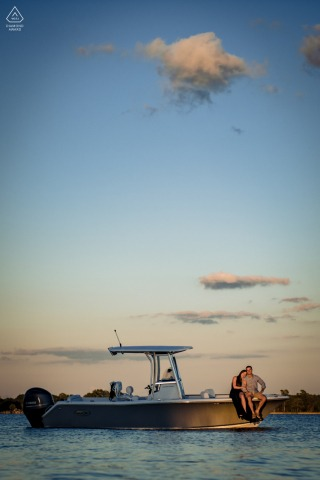 Eastern Shore Engagement photography of a couple sitting on a boat in the water with clouds overhead