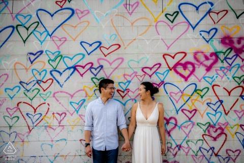 Washington DC pareja posando delante de una pared cubierta de corazones de colores dibujados a mano