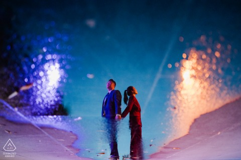DC engagement portrait with a posed couple using a puddle reflection in Kennedy Center, DC with a Sparkler in water
