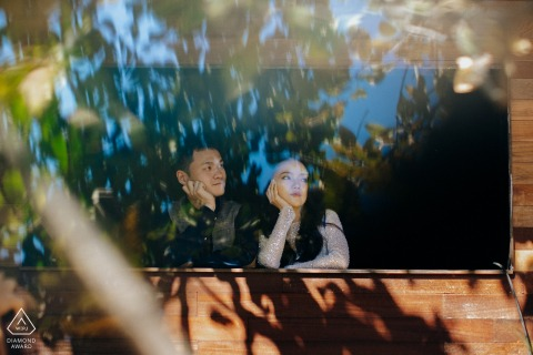 Xi'an engagement photography of a couple looking out a window with tree reflections