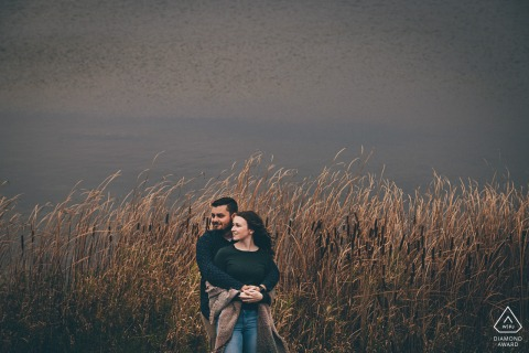 Ontario engagement photo shoot in Orangeville, Ontario with a Couple in a windy field
