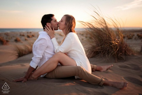 France engagement portrait with a posed couple sitting on the sands of Espiguette beach south of France and kissing