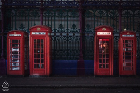 UK pre-wedding photo session with an engaged couple inside vintage red phone booths in London