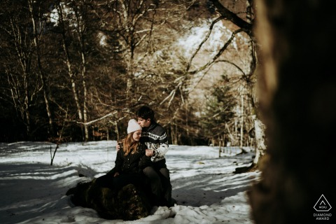 FR engagement photoshoot & pre-wedding session in Pyrenees France with a couple on a trunk in the snow