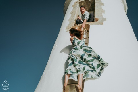 FR pre-wedding photo session with an engaged couple in Vendee, Francewith a man on a lighthouse