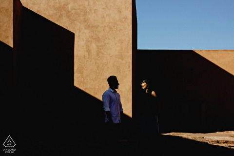 Africa engagement portrait with a posed couple in interesting light and a shadow geometric composition in Marrakech, Morocco