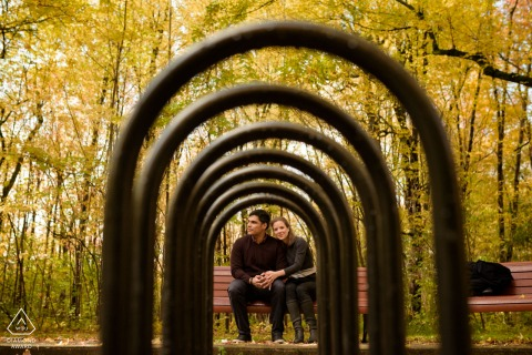 Canadian photo shoot at Angrignon Park, Montreal, Quebec with an Engaged couple sitting on park bench, framed by bike racks with yellow fall leaves behind them