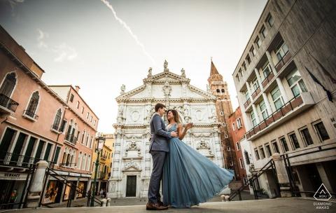 Sesión de fotos de compromiso de Italia desde un ángulo bajo con una pareja vestida formalmente en Venecia