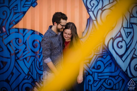 AZ pre wedding and engagement photography of a couple in front of a mural  in Downtown Phoenix