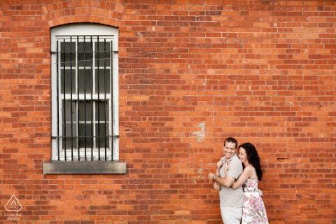 RI sesja zaręczynowa pary przed ceglanym murem i oknem w Newport, Rhode Island