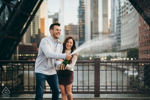 Illinois engagement photoshoot & pre-wedding session of a couple spraying champagne at Kinzie Street Bridge in Chicago
