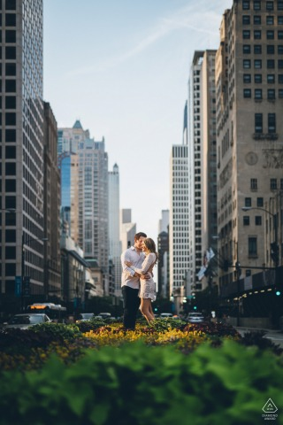 Illinois engagement portrait with a posed couple amongst the tall skyscrapers of Michigan Ave in Chicago