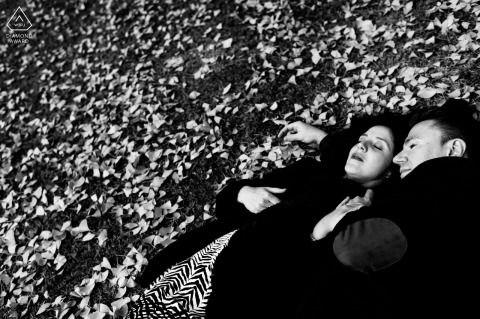 PT engagement photo shoot at Parque Eduardo VII, Lisboa, Portugal of a couple lying on the ground strewn with fallen leaves from the trees, during the autumn