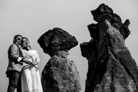 Séance de portrait de mariage avant la Turquie avec des amoureux engagés étreignant par de hauts rochers en Cappadoce, Turquie