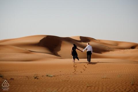 UAE pre wedding portrait session with engaged lovers in the Maleiha Desert, Dubai walking through the sand dunes