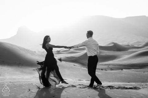 Pre-huwelijks- en verlovingsfotografie in de VAE uit Maleiha Desert, Dubai van een dansend stel in de woestijn