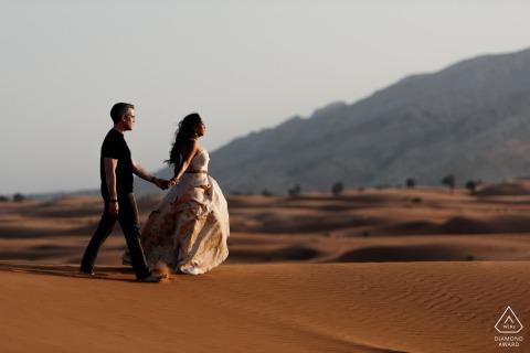 Pre-bruiloft fotosessie in de VAE met een verloofd stel in Fossil Rock, Dubai Desert terwijl ze aan de rand van de duinen wandelen