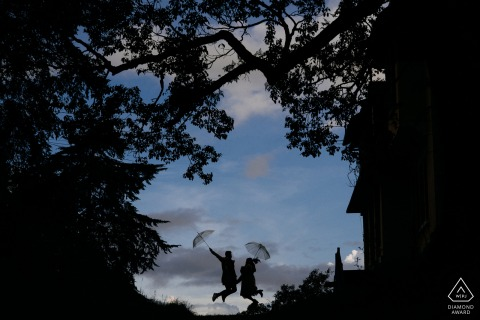 Vietnam silhouette engagement portrait with a posed couple jumping with umbrellas in Dalat