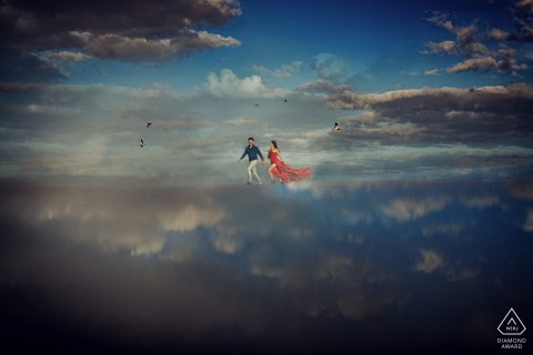 Goias wedding photographer at a pre-wedding session with an engaged couple running through the clouds high above Caraíba