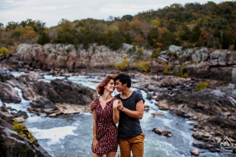 Virginia water engagement photo shoot as A couple embraces at Great Falls