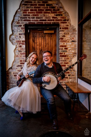 DC pre wedding portrait session of engaged musicians in Blagden Alley laughing and playing a mandolin & banjo