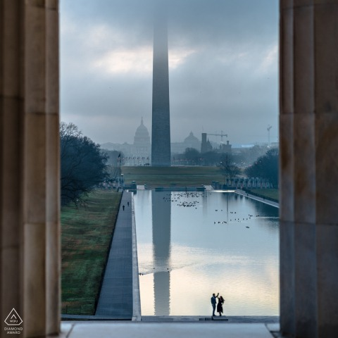 DC pre wedding portrait session of engaged lovers at the Lincoln Memorial DCwith A view from the inside, looking out at the reflecting pool at the couple twirling