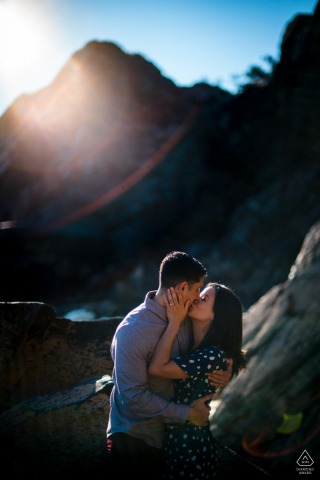 Virginia engagement portrait with a posed couple at Great Falls VA with a kiss in front of a large rock, lens flare accents the upper left corner