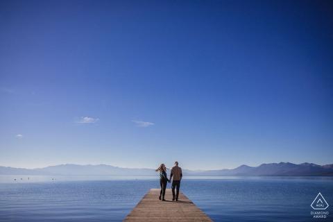 CA sesión de fotos previa a la boda en Skylandia Beach, Tahoe City, CA con una pareja caminando por un muelle con montañas y un gran lago azul de fondo