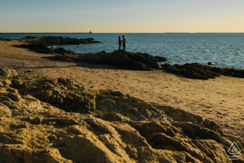 A couple stands together in the distance by the ocean with rocky formation and sand around them in Lighthouse Point Park, New Haven, Connecticut for pre-wed images