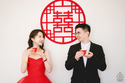 En casa, una pareja bebe té durante una sesión creativa de retratos antes del matrimonio.
