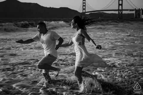 Baker Beach, San Francisco, California, pareja al atardecer correr en la playa durante una sesión de fotos antes del matrimonio