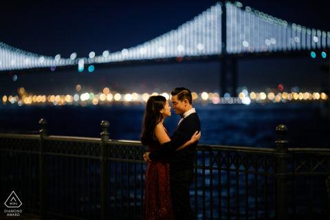 Pier 7, San Francisco, California, pareja con una vista nocturna del puente de la bahía durante una sesión previa al matrimonio