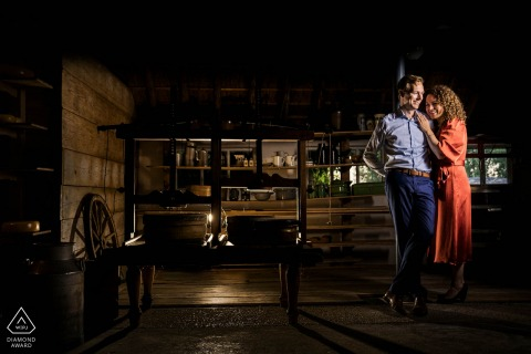 Inside an old cheese farm, The couple is standing next to a press to make cheese during a pre-wed engagement photo session