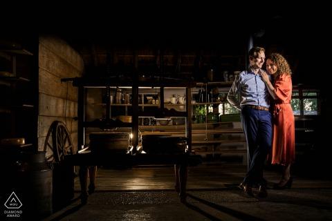 In een oude kaasboerderij staat het stel naast een pers om kaas te maken tijdens een fotosessie voor een verlovingsfotosessie