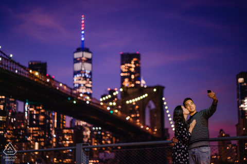 dumbo, nyc couple taking a selfie at dusk during a pre-wed picture session