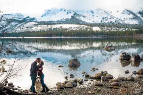 Fallen Leaf Lake, California Couple share a loving embrace that's interrupted by their Husky moving in between their legs
