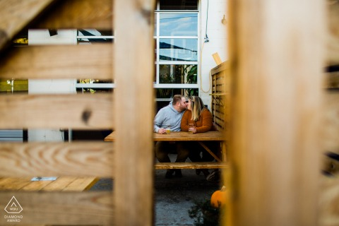 Zuni Street Brewing Couple kissing on brewery patio for a pre-wed picture session