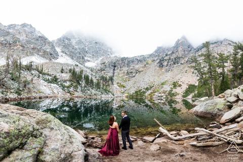 Parco nazionale delle montagne rocciose, Estes Park, Colorado, la futura sposa ha realizzato a mano il suo vestito rosso per mettersi in risalto sullo sfondo sempreverde durante il loro fidanzamento mattutino nebbioso a Emerald Lake