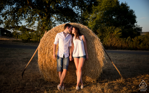 Marciac, Gers, France couple kissing in front of a hay bale for a creative engagement shoot